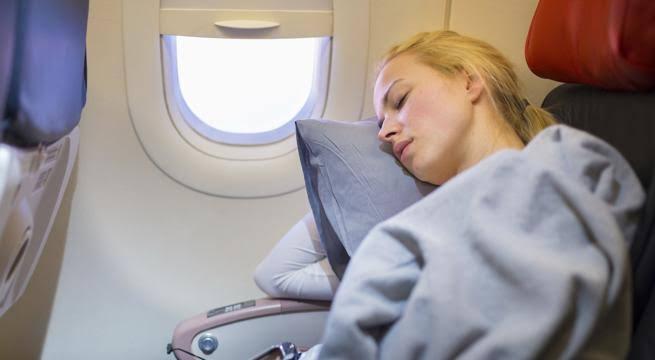 Mujer dormida en un avión