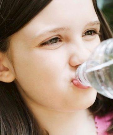 Niña bebiendo agua de una botella