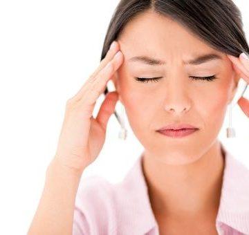 Chica con migraña y manos en la cabeza