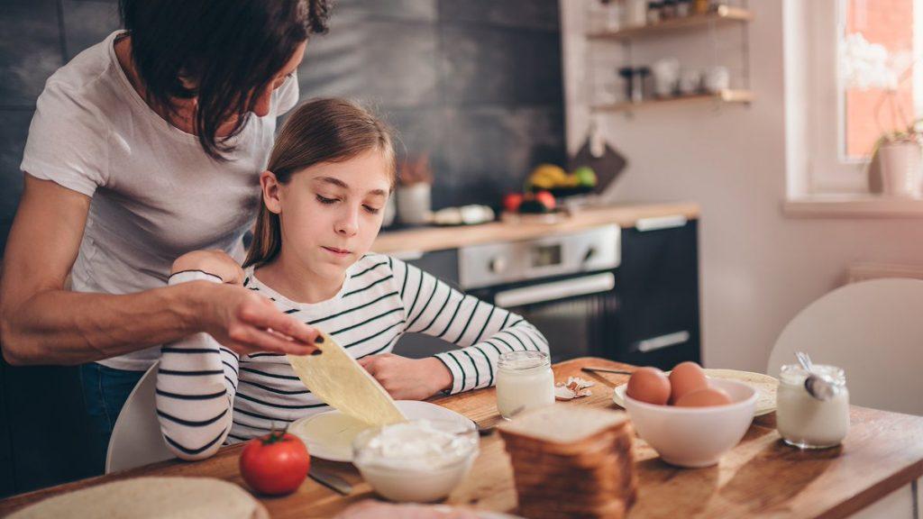 Mamá dando de comer a su hija