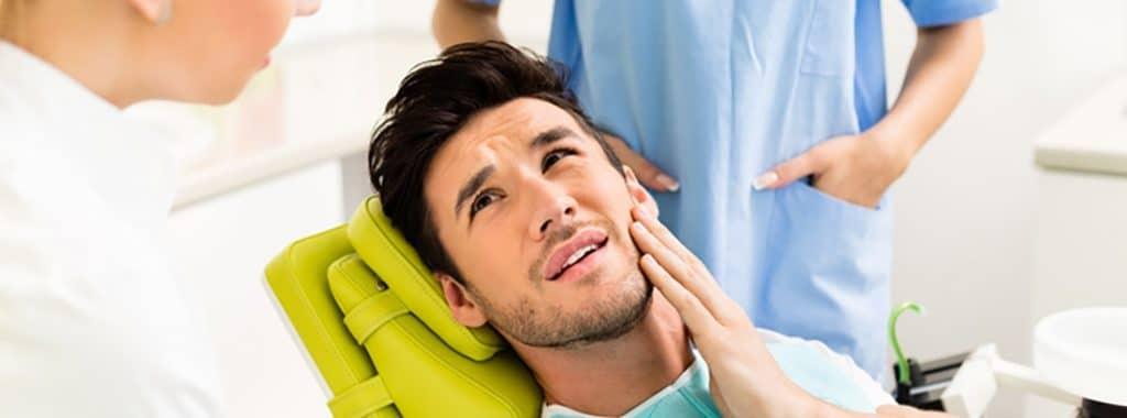 hombre en el dentista con dolor de diente