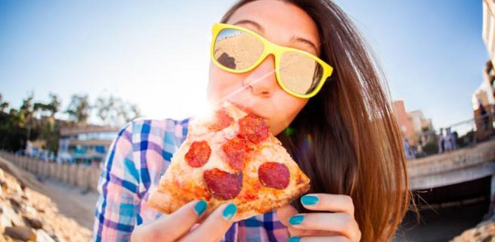 chica comiendo pizza de pepperoni